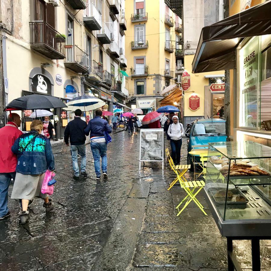 regenachtige dag in napels met toeristen met paraplu's